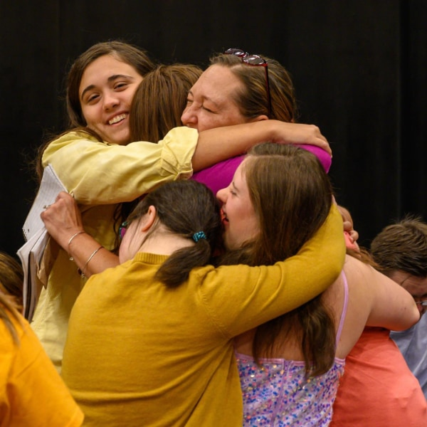 OpenSpot Theatre instructor hugging students